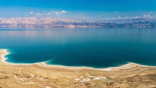 עננים לבנים כמו מלח והרים אדומים משתקפים במים בגוון טורקיז מושלם ותכלת בהיר, חוף צהבהב עם עיטורים לבנים נוגע בריחוף במים. תמונה ברורה וצבעונית לסלון מעוצב בסגנון וינטאג' צעיר ורענן