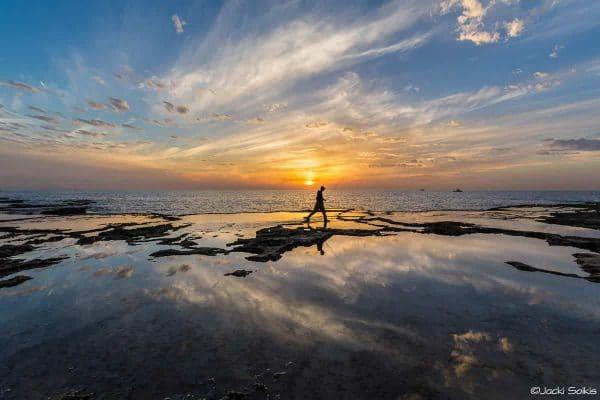 הדייג מתהלך לו בין מים לשמים לבית המודרני והחדיש תמונה שמחה וקצבית בגווני צהוב כחול ואופק אינסופי