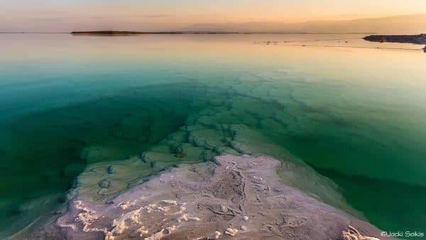 מים שקטים צבועים ירוק עמוק נוגסים בנציב מלח אפרפר, ומשתרעים עד לקצות ההרים החומים זהובים ברקע תמונה נפלאה על קנבס מתוח בסגנון גלריה תפאר את הסלון האלגנטי שלך