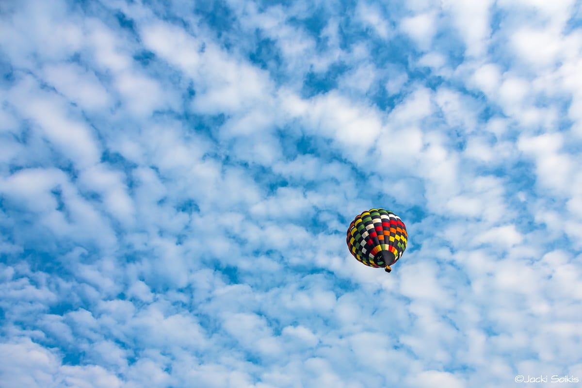 מעשה בכדור פורח שעף למחוזות הדמיון, בולט בצבעוניות קסומה על רקע השמיים התכולים לבנים תמונה מעוררת השראה לעיצוב הבית.