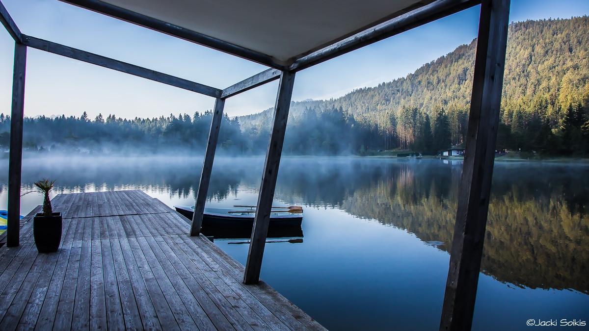 ערפילי בוקר מרחפים בלובן אפרורי מעל אגם צלול כמראה כחולה כהה שמתמזג לכחול אינדיגו בהיר ועצים כבירים בירוק אשוח ממוסגרים במוטות העץ של המזח. תמונה ממבחר תמונות של נופים המתוחה על קנבס לסלון מעוצב בסגנון מודרני נקי