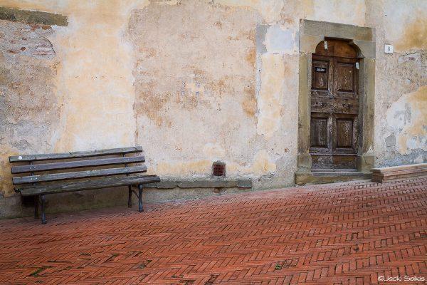 ריבועים ופסים בטקסטורות ומרקמים שונים דלת עץ חומה עתיקה מגולפת מעשה אמן, רצפות בגוון טרה קוטה. צבעים חמים ומעוררים על רקע קיר אותנטי. תמונה לסלון עם צבעוניות מאופקת תתאים לסלון בסגנון אלטרנטיבי מודרני