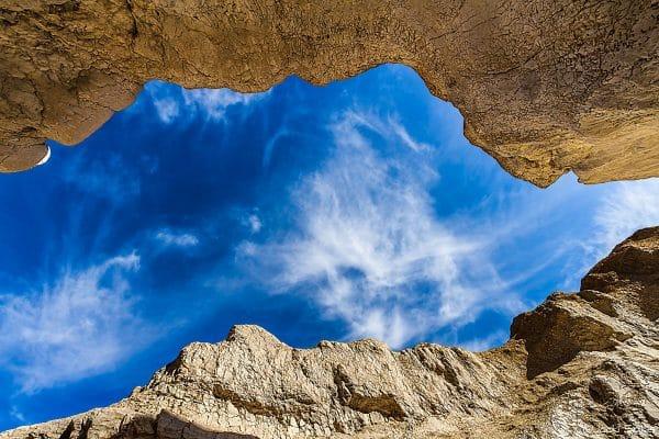 חרך מתוך ההר נותן הצצה לשמיים כחולים עמוקים, ניגוד בין חום צהבהב לכחול והצללים המרתקים נותנים תחושה של חלון לעולם אחר, תמונה חזקה לבית מתוחה על קנבס.