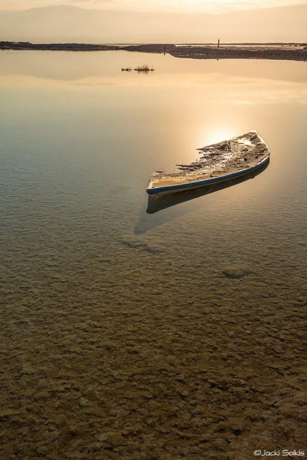 תמונה בסגנון נקי ומדוייק לפינת אוכל כפרית או סלון בסגנון קלאסי, ים בצבעי זהב מלחך בערגה שרידי סירה במרחב אינסופי של מים ושמים