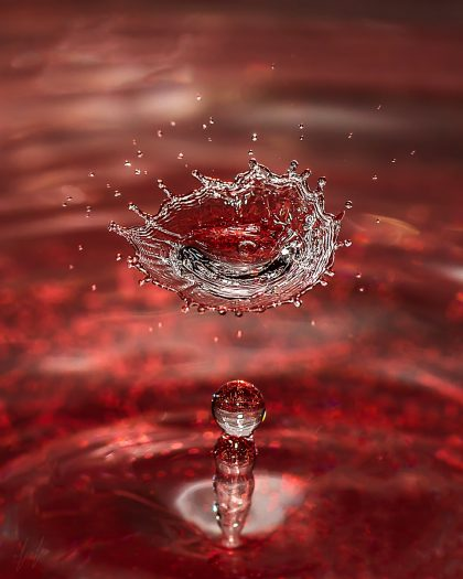 תמונה לסלון של טיפות מים על רקע אדום עמוק