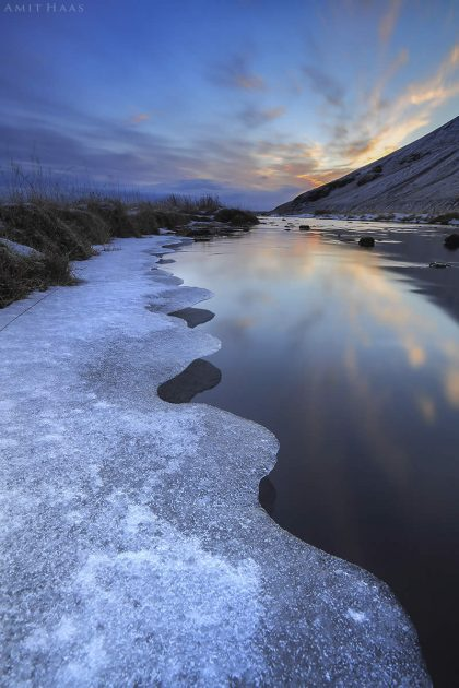 בשולי הנהר הרחב נוגס משטח הקרח בפני המים בדרכו לצבוע את הנהר כולו בלבן קפוא. תמונה באווירה חורפית קסומה המתאימה לסלון הבית או למשרד