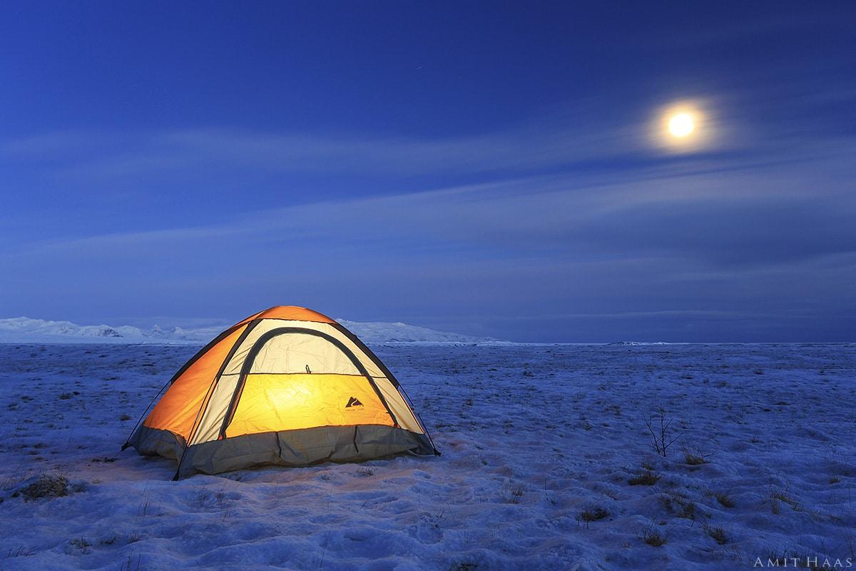 מרחבים אינסופים של שלג וקרח בליל ירח מלא מוארים לאורו באור חמים מבעד למעטה עננים היוצרים אוירה מיוחדת שתתאים לסלון ביתכם