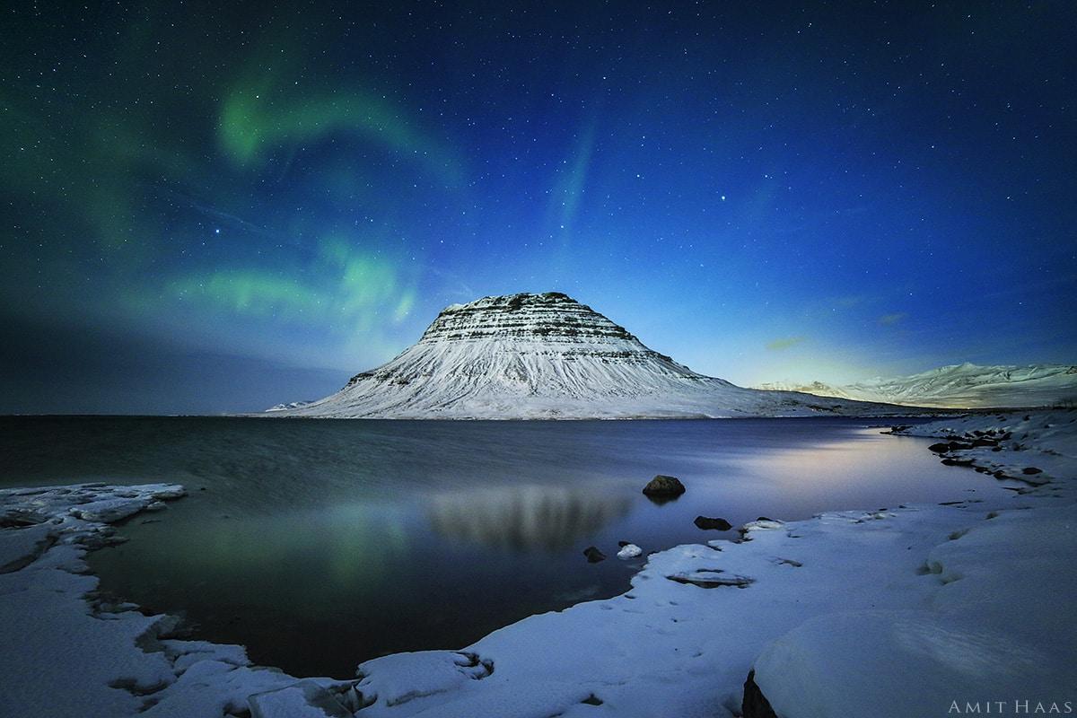 אורות אורורה בוראליס הנראות כפריזמות של אור היוצאות מפסגתו של הר הפירמידה כפי שנראתה בליל חורפי מעל שמי איסלנד. צילום נוף יחודי מתוח על קנבס לסלון ביתכם