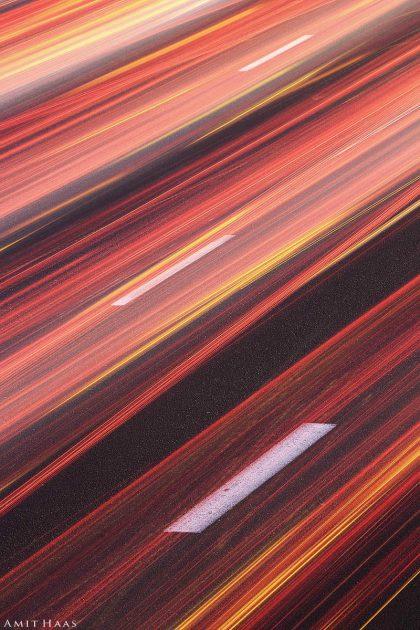 קרני אור אינסופיות נמתחות בזמן ובמרחב בשלל גוונים של כתום ואדום, תמונה מופשטת ומסקרנת זו יכולה להתאים לסלון צעיר ותוסס