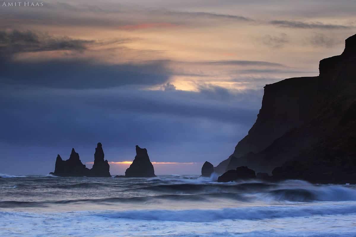 צוקי אבן כהים מתרוממים מתוך הים האפור-כחול הגועש, וגליו נשברים על שולי הסלע בעוצמה. תמונה קסומה לסלון המשלבת את גווניו הקרים והחורפיים של הים עם הנהרה הכתומה של שמי הערב ויוצרת אווירה של שקט שלפני הסערה