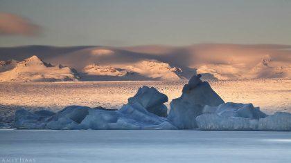 רכסים מכוסי שלג, משטחי קרח שטוחים וגדולים וקרחונים שלוטשו בידי כוחות הטבע מרכיבים תמונת נוף מרהיבה זו. תמונה לסלון ובה פלטת צבעים רכה של כחול, לבן, אפור וכתום