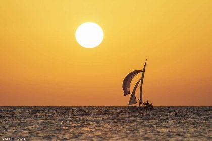 זוג שייטים על סירת מפרש בים אפרפר נהנים מקרני השמש הלבנה-צהובה המתקרבת לשקיעתה. השמיים הכתומים הנקיים מעננים יוצרים אווירת בין ערביים נינוחה שתשרה רוגע בסלון ביתכם