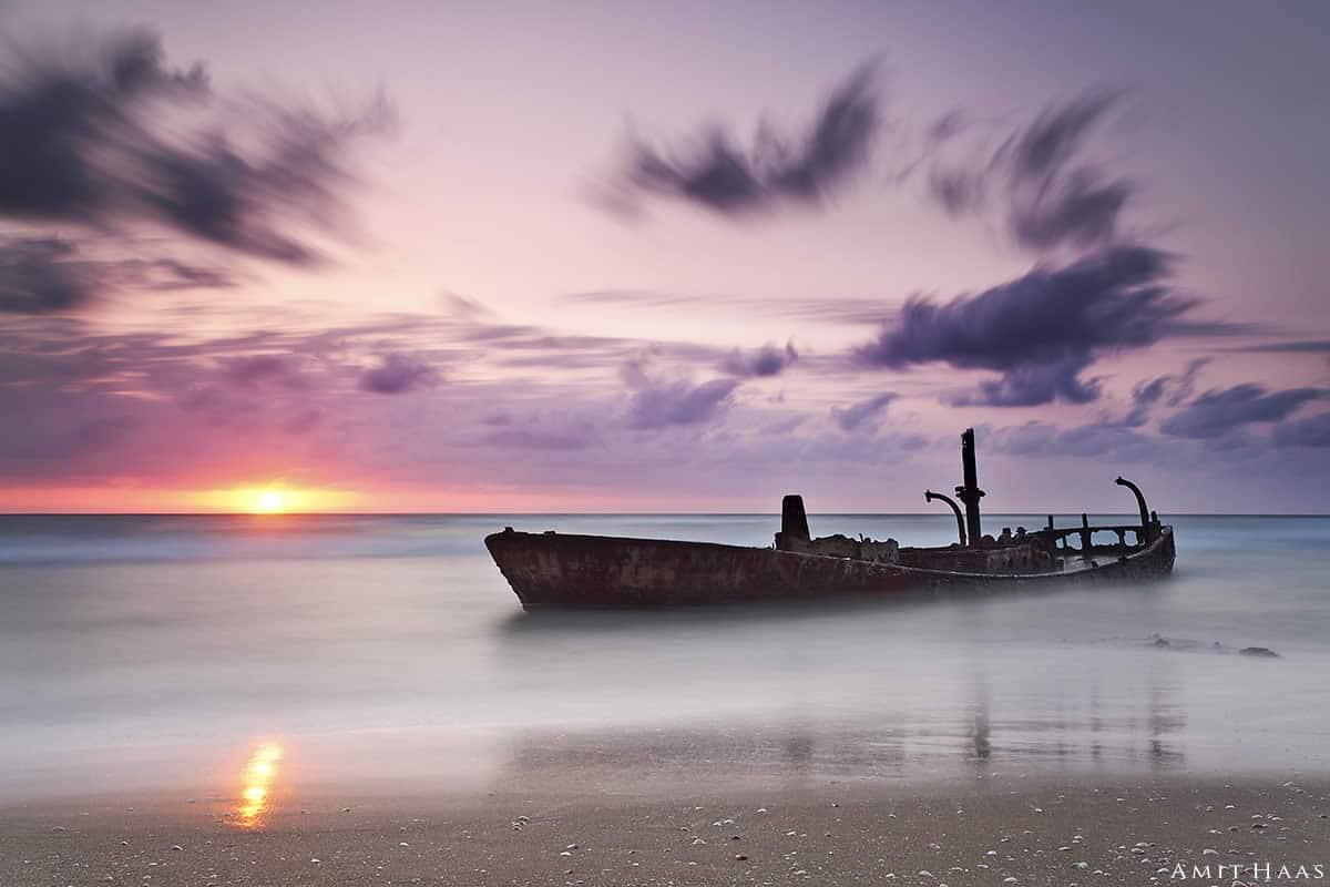 תמונות של ים מלאות בקסם מיוחד של שלווה ושל תנועה שקטה ועמוקה. בתמונה מלאת מסתורין זו סירה חלודה צפה על פני המים הרוגעים כשמעליה פרושים שמיים סגולים-ורודים מהממים. תמונה חלומית בצבעים רכים לסלון או למשרד