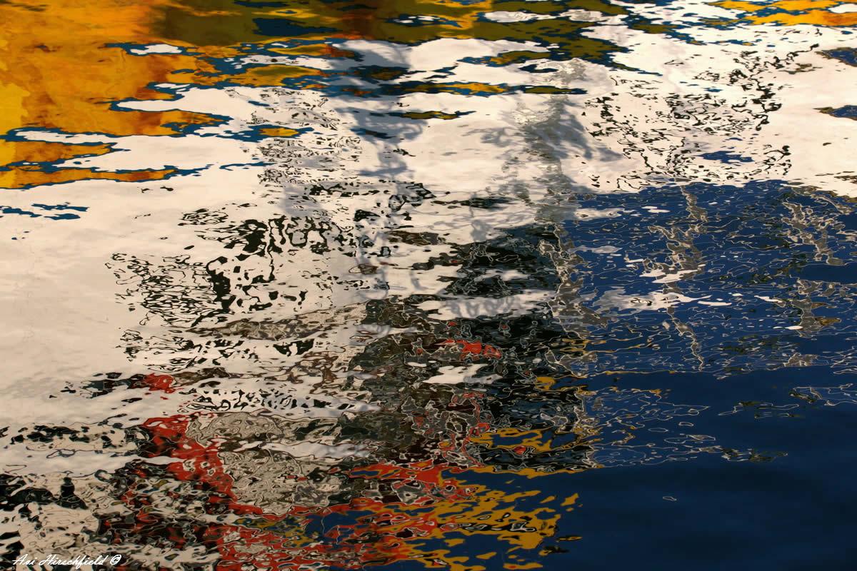 על פני המים נשבר העולם לרסיסי צבע מרהיבים בגוני כחול, חום, ירוק וכתום היוצרים מערבולת מלאת תנועה של צבעים. תמונת אבסטרקט מרהיבה לסלון בסגנון מודרני
