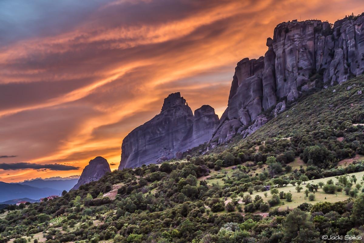 הרים סגולים מתרוממים מתוך שדה ירוק ונוגעים בשמיים זרועי עננים כתומים צהובים של שקיעה מלאת הוד, שילוב הצבעים והמרקמים יוצרים תמונה מושלמת לסלון האקלקטי