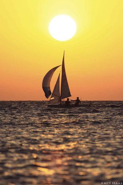 מפרשית הנראית כמיניאטורה במרחב הים, וכמחוגים היוצאים ממרכז השמש השוקעת אט אט מאחוריה. צילום מינימליסטי בגוונים חמים לסלון ולחדרי השינה