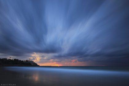 צלליתה של העיר העתיקה ביפו ניצבת אל מול אורותיה האחרונים של השקיעה הכתומה ומול הכחול האינסופי של הים והעננים, שתנועתם פורצת החוצה מהתמונה. מתאים לחדר השינה ולסלון בדירתכם
