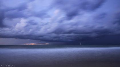 בין המסה העוצמתית של ענני הגשם הכבדים לבין הים האינסופי נמתח לו ברק אחד המקשר בין שני העולמות - השמימי והארצי. צילום באווירה חורפית לחדר השינה ולסלון