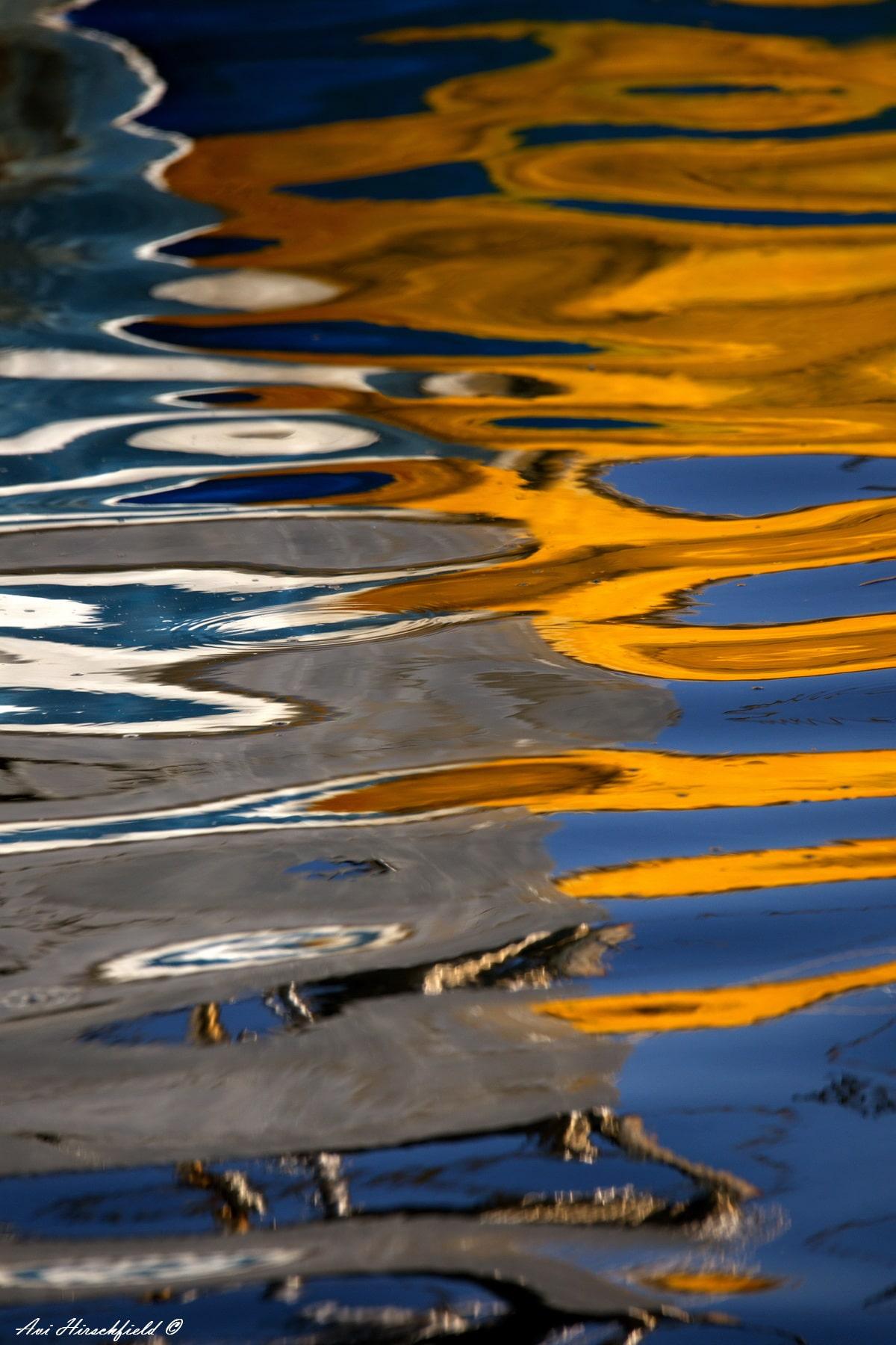 השתקפויות צהובות מרצדות על פני המים הכחולים שתנועתם העדינה שוברת את בבואת העולם הנשקף בהם. ערבוביה אבסטרקטית ומלאת רוך של צבעים וצורות שתיראה נפלא בהדפסה על זכוכית אקרילית