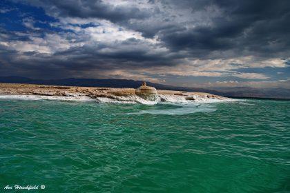 חלקת אדמה סלעית מתרוממת ועולה מבין גלי הים, שצבע מימיו ירוק טורקיז משגע. ממעל עננים כבדים ואפורים מכסים את הרקיע וממסגרים את היבשה היציבה בין תנועת הים והשמיים. תמונות של ים יכניסו עוצמה רכה כל סלון או משרד, ותמונה זו במיוחד