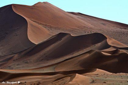 המדבר הנמיבי מתעורר ליום חדש וחושף בהדרגה את גוני החום והכתום השולטים בקימורי השטח הדרמטיים, שאת צורתם מפסלת הרוח החמה. תמונה מרשימה ומפעימה זו המדגישה את תנועתו האינסופית של הטבע מתאימה לסלון או למשרד המעוצבים בגוונים בהירים