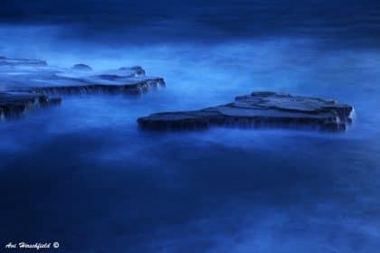 בשעת לילה תחת אורי ירח בהיר עולים מבין גלי הים הכהים סלעים משוננים ונשטפים במים המלוחים. תמונה בגוני כחול עמוקים ומרהיבים שתעניק טאץ' עיצובי מלא רושם לכל סלון