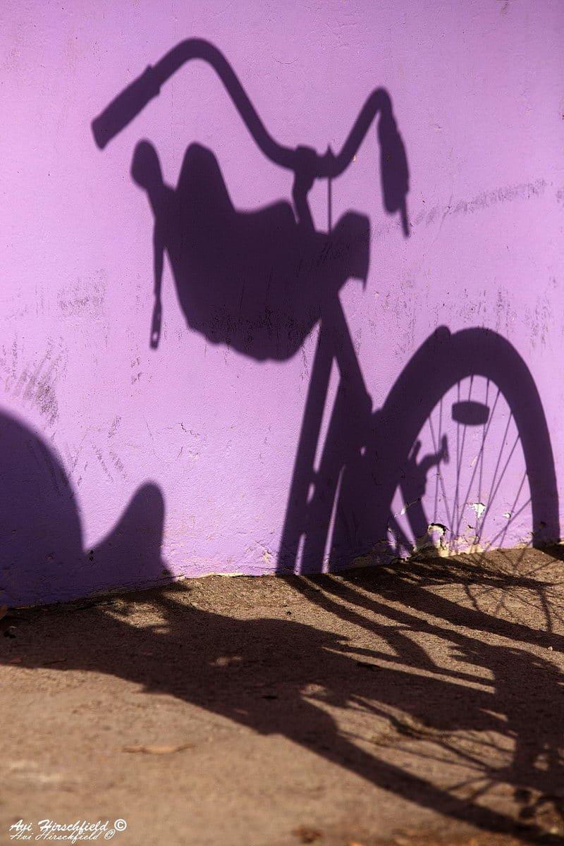 קרני השמש החזקות מטילות על הקיר הסגול ועל המדרכה החומה את צלליתם המדויקת של זוג אופניים. תמונה עירונית בצבעים חיים המתאימה לסלון בסגנון אורבני צעיר