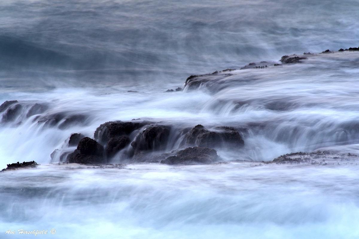 בשעת הגאות שוטף הים את הסלעים החומים הניצבים לחופו ועוטף אותם בקצב גלים לבן ורך. תמונה שתכניס אווירה מסתורית ומלאת עומק לסלון ביתכם
