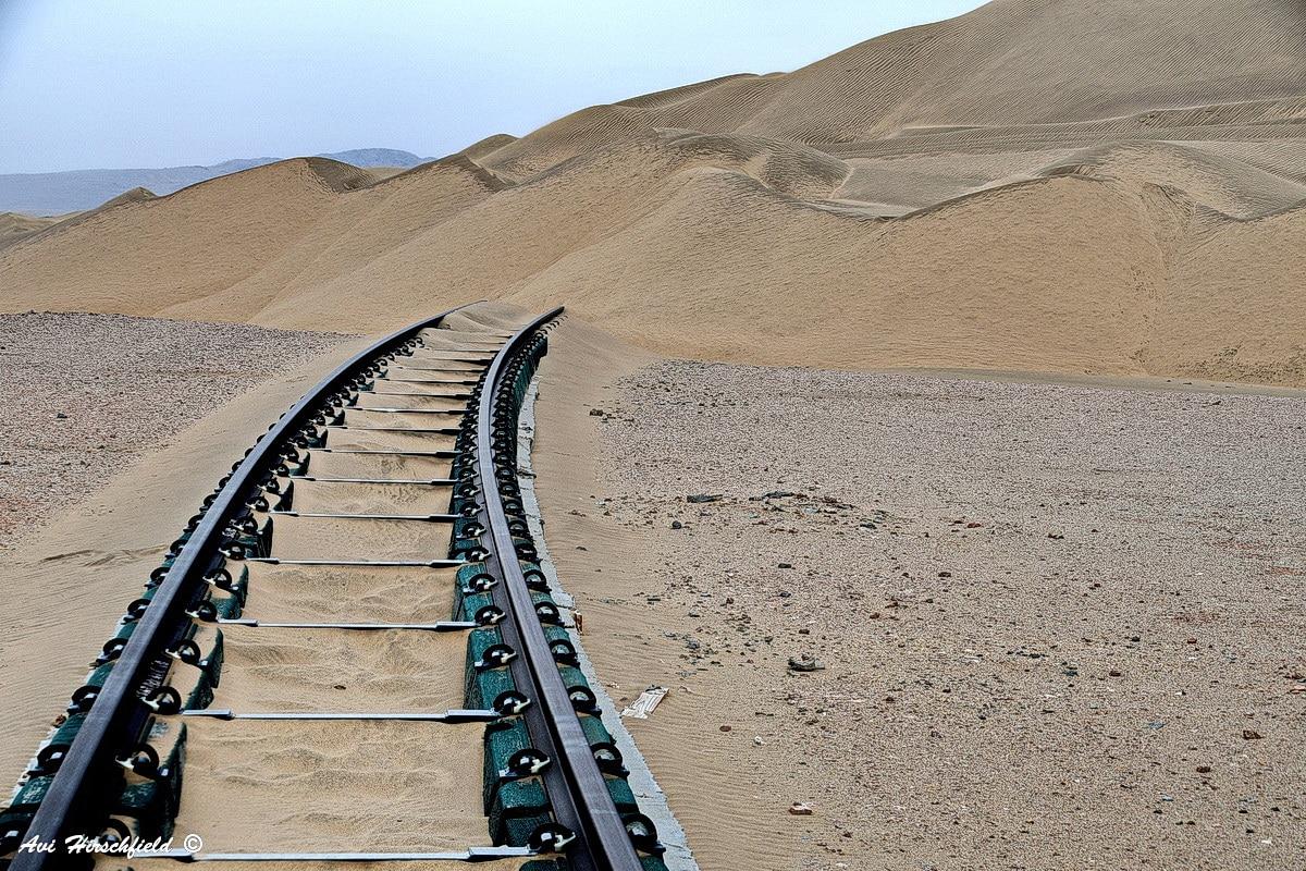 מסילת ברזל מרופדת חול דקיק חותכת את המדבר על גווניו החומים הבהירים ושיפוליו הרכים ונראית כנעלמת במדרון המשתפל. תמונה מינימליסטית המתאימה לסלון בעיצוב תעשייתי