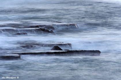 בשעת סערה בים מתגלה עושר של גוני כחול אפרפרים. גלי הים העוצמתיים נשברים על הסלעים ומותירים אחריהם קצף רך ובהיר המשרה אווירה חלומית על תמונה מפעימה זו. תמונה שתשרה אווירה דרמטית על סלון בעיצוב מודרני או תעשייתי