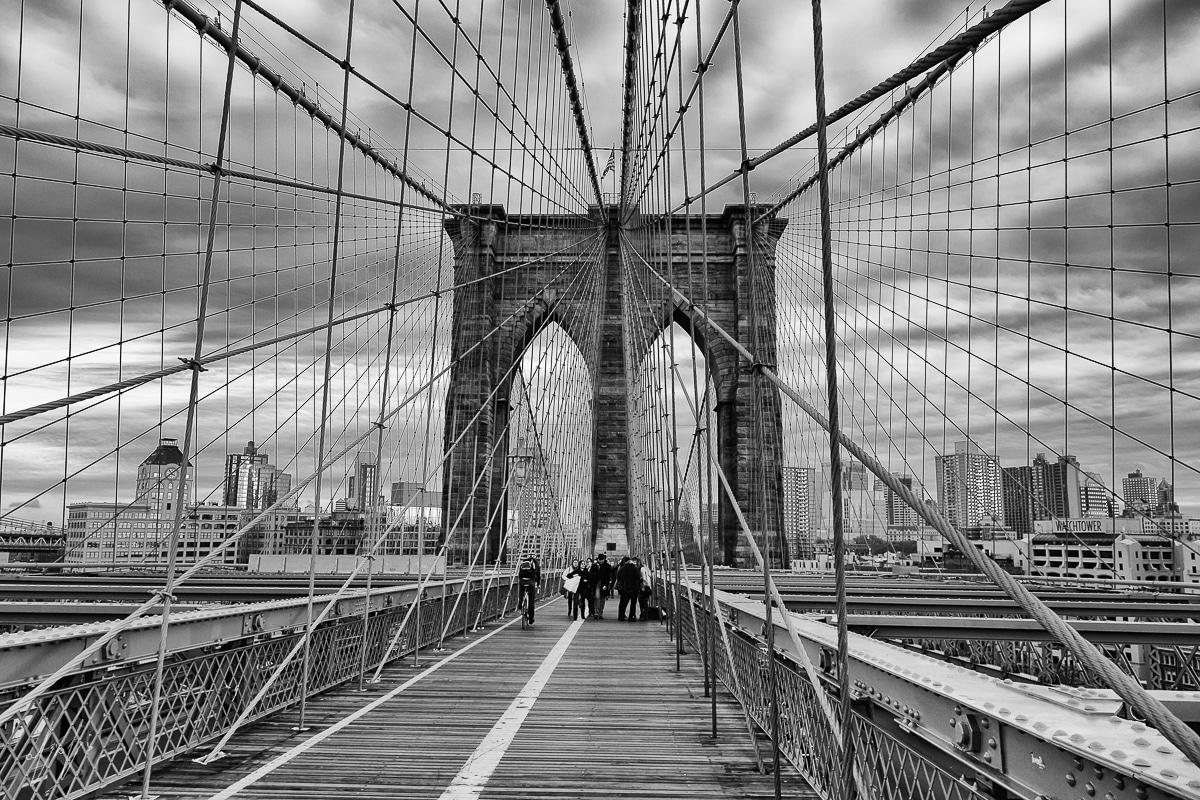 גשר מתוח מעל נהר רחב, כבליו החזקים שומרים על יציבותו, וברקע עיר תוססת ושמיים מכוסי עננים. תמונת שחור לבן מרשימה ובעלת עוצמה המתאימה לסלון או משרד בעיצוב מודרני או תעשייתי