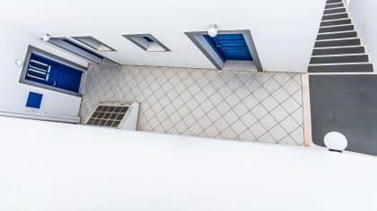מבט עילי על קומת מגורים יוצר חגיגה גרפית של צורות וקווים. ריצוף, מדרגות, דלתות וחלונות מופשטים משימושם המקורי ומתגלים ביופיים הגיאומטרי. תמונה מיוחדת בצבעים סולידיים המתאימה לסלון או למשרד בעיצוב מודרני