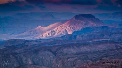 רכסי הרים סלעיים וצחיחים נצבעים בכחול עמוק של אפלה ומדרון אחד נהנה מקרני שמש ישירות הצובעות אותו בכתום עז. תמונה מרהיבה של נופי אילת שתכניס את אווירת החופש המדברית למשרד או לסלון