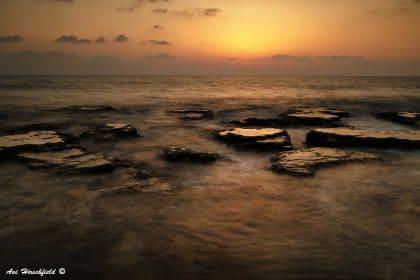 שקיעה זהובה צובעת את האופק בכתום עמוק ואת הים בגוונים כהים. סלעים חלקים שנשחקו בגלי הים מבצבצים ונבלעים בתנועת המים האינסופית. תמונה שתכניס חמימות לסלון או לחדר השינה