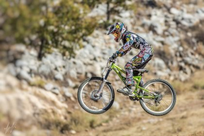 רוכב אופניים מבצע קפיצה מרשימה במהלך רכיבת שטח על רקע צמחייה, סלעים ואדמה בגוני חום וירוק. תמונה דינמית לאוהבי האקסטרים שתהלום סלון או משרד באווירה צעירה