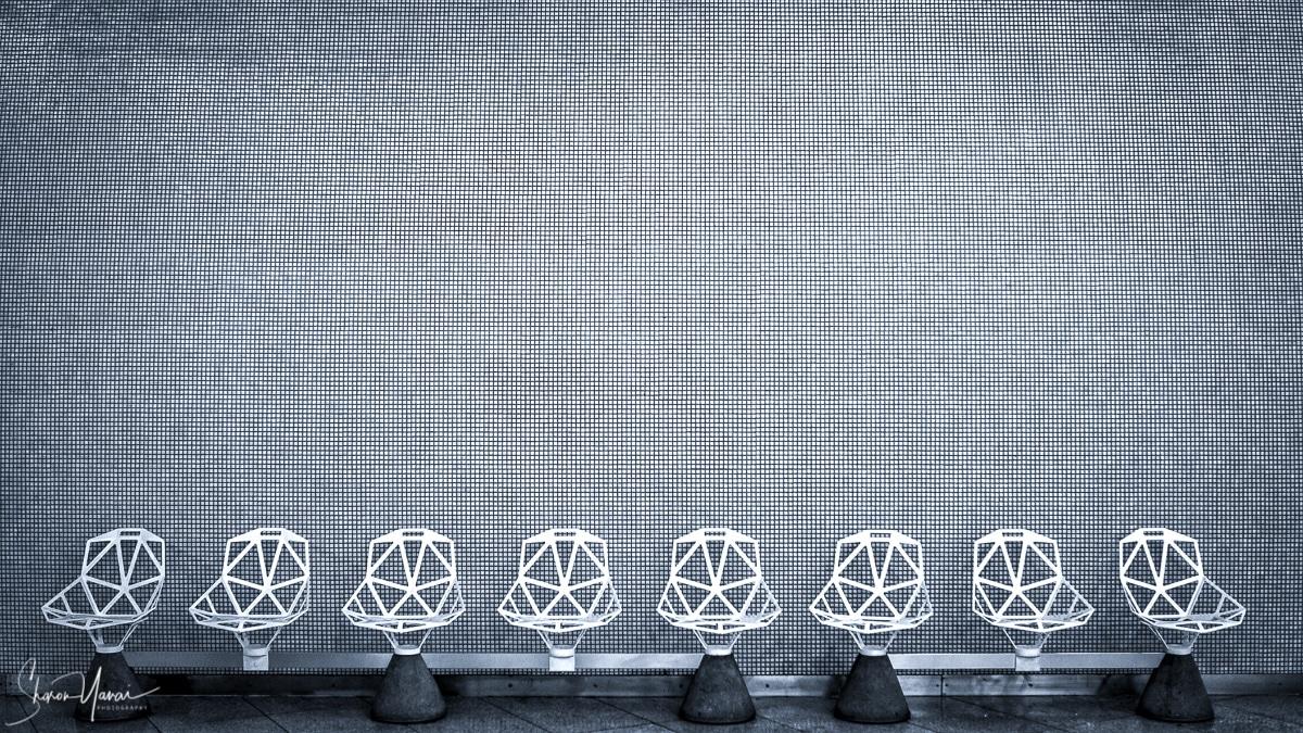 עבודה מינימלסטית בשחור לבן המציגה שישה כסאות ריקים בעיצוב מיוחד על רקע קיר משובץ. תמונה מתאימה למשרד ולחדר המתנה.