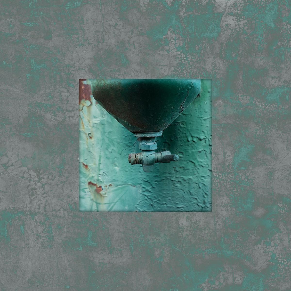 קטע מדוד מים ישן נושן שנצבע באותו צבע ומירקם של הקיר הכחול מאחור. תמונה ריבועית עם מסגור טקסטורלי ירוק-אפור לחדר עבודה ולמשרד.