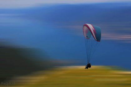 בין שמיים לארץ, בשקט ושלווה, תלויים על מצנח רחיפה ונהנים מהנוף והאויר הפתוח. התמונה צולמה גבוה מעל אגם גארדה ומתאימה להוספת רוגע ושלווה למשרד או לבית.