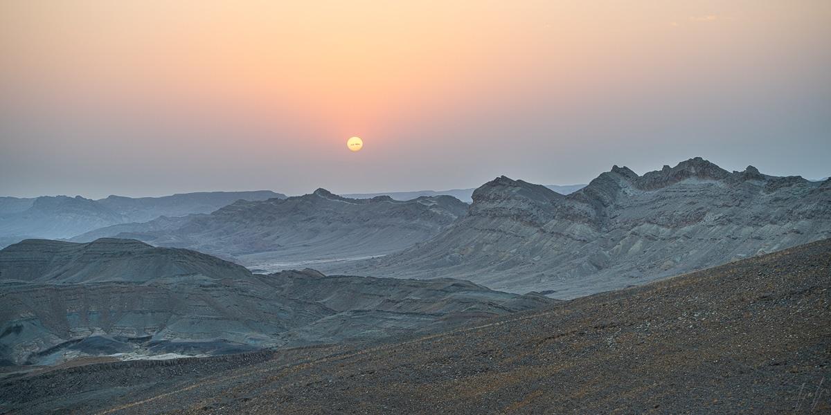 תמונת שקיעה מרהיבה במדבר מכתש רמון עם שמש כתומה מעל ההאדמה הלבנה של המכתש