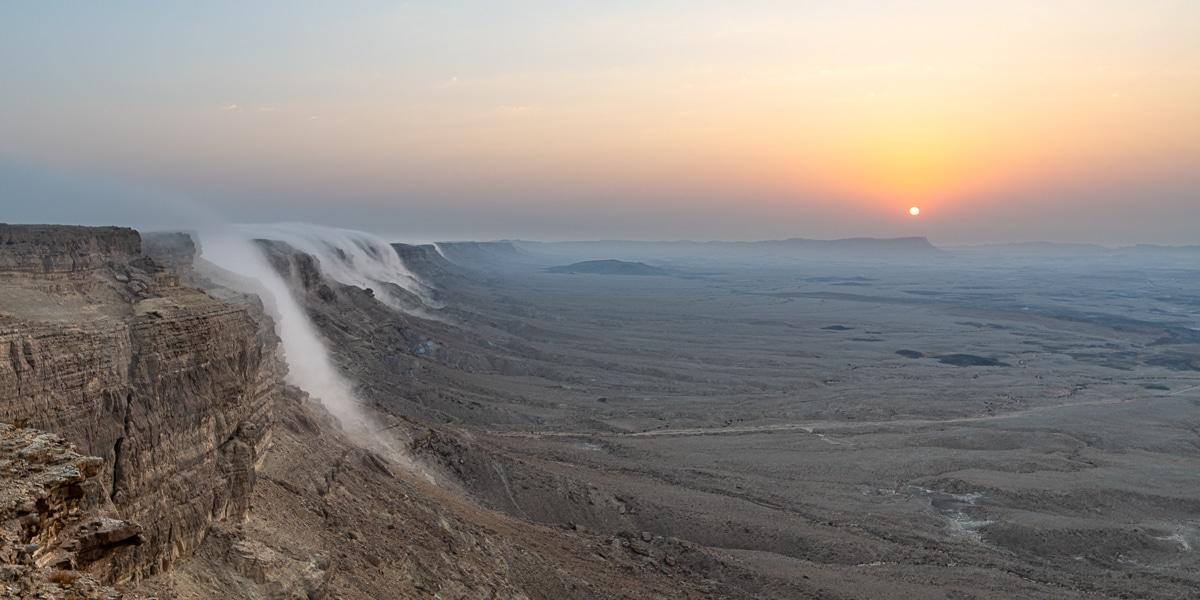 תמונה של זריחה במכתש רמון עם מפלי העננים המפורסמים שיורדים משפת המצוק עד למרגלות המכתש